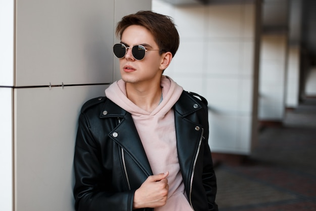 Homem elegante jovem hippie com um penteado na moda em elegantes óculos pretos em uma jaqueta de couro preta em um moletom rosa fica perto de uma parede branca. um cara americano atraente. moda masculina.