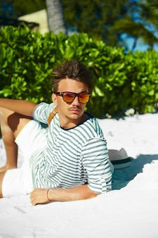 Homem elegante jovem modelo masculino, deitado na areia da praia, usando chapéu de verão hipster, aproveitando as férias de verão viajar perto do oceano em óculos de sol