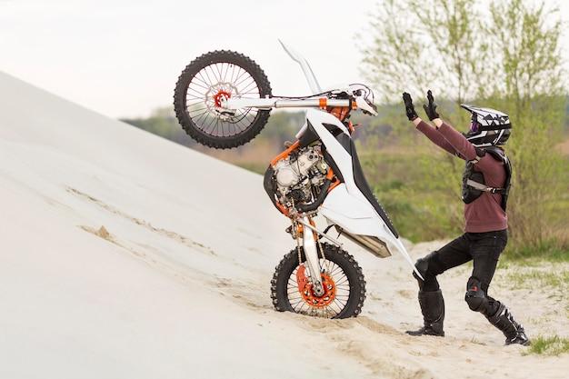 Homem elegante, levantando a moto no deserto