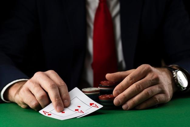 Homem elegante na mesa de jogo verde com fichas de jogo e cartas, jogando pôquer e blackjack no cassino.