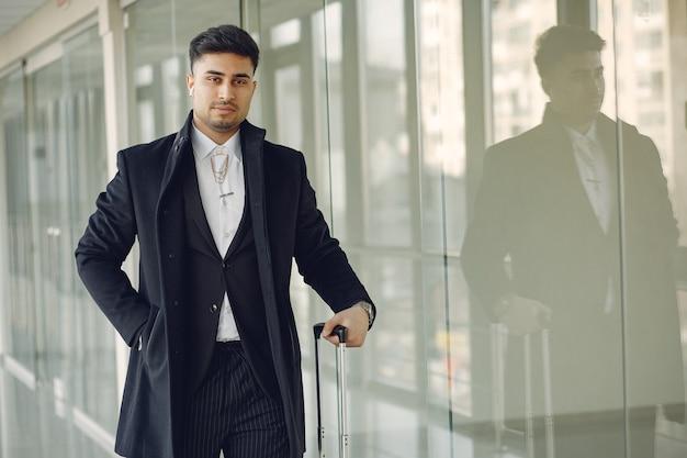 Homem elegante no aeroporto com uma mala