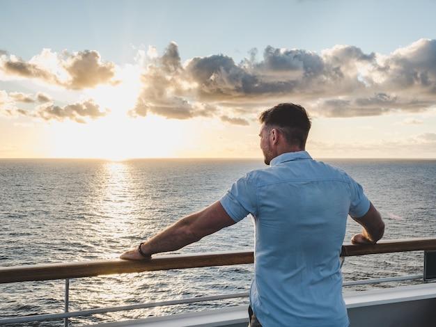 Homem elegante no convés vazio de um navio de cruzeiro contra um fundo de ondas do mar