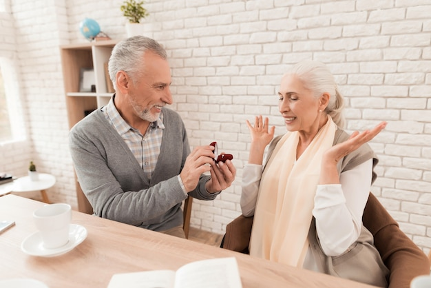 Homem elegante oferece a mão para amadurecer mulher bonita.