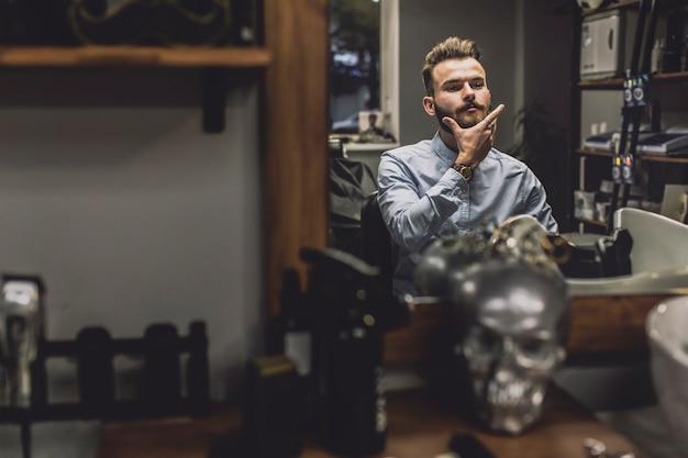 Homem elegante olhando reflexão na barbearia