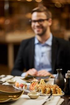 Homem elegante prestes a jantar um saboroso sushi em um restaurante