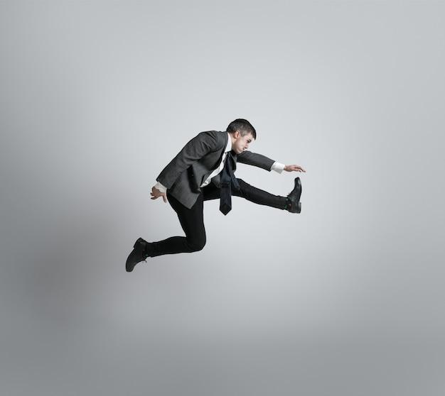 Homem elegante pulando na parede cinza