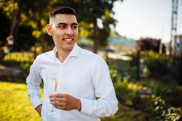 Homem elegante segurando taças de champanhe no casamento de luxo.