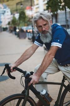 Homem elegante sênior com cabelo grisalho e barba andando de bicicleta de cascalho