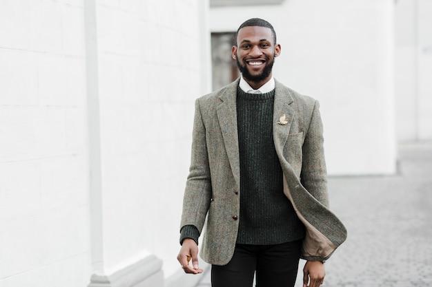 Homem elegante sorridente posando ao ar livre