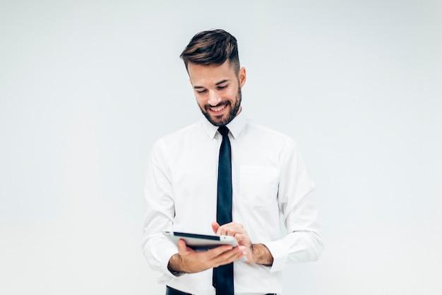 Homem elegante sorrindo enquanto assistia a um tablet