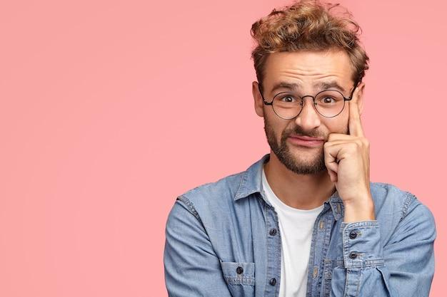 Homem elegante tem cabelo encaracolado e a barba por fazer toca as têmporas e olha com seriedade, tem expressão facial intrigada, vestido com uma camisa jeans estilosa, posa sobre a parede rosa com espaço de cópia à parte