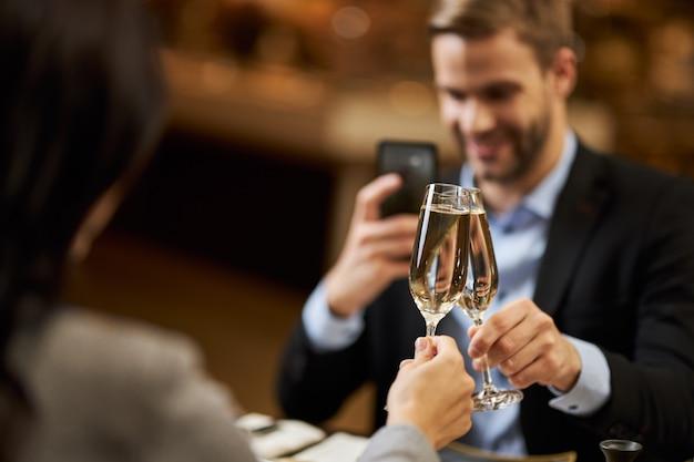 Homem elegante tirando foto de duas taças de champanhe