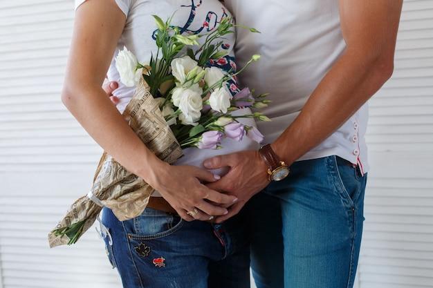 Homem elegante toca a barriga da mulher grávida. duas mãos na barriga da mulher grávida close-up. lindo casal esperando um parto. família jovem feliz esperando bebê.