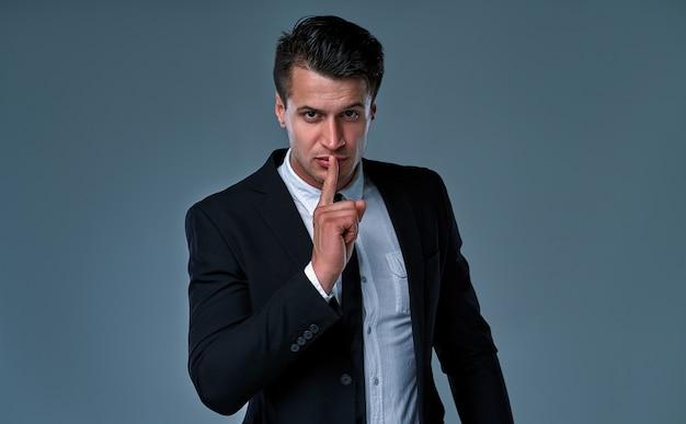 Homem elegante, vestindo smoking na sala cinza