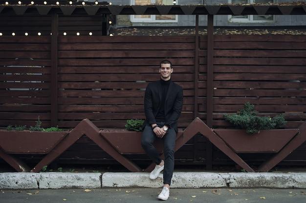 Homem elegante, vestindo um terno, sentado contra a parede de madeira
