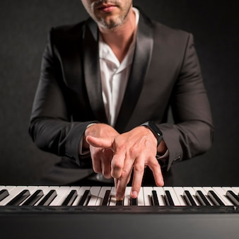 Homem elegantemente vestido tocando teclado digital