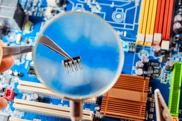 Homem eletricista consertando a placa microeletrônica, segurando o microchip na pinça e consertando a placa-mãe eletrônica.