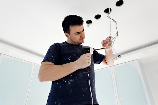 Homem eletricista consertando luz