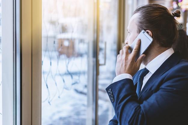 Homem, em, a, paleto, chamando, telefone móvel, olhar, a, janela
