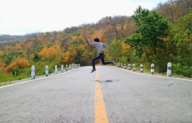 Homem, em, a, pose, de, pular, através, a, estrada montanha, entre, cor, mudança, floresta