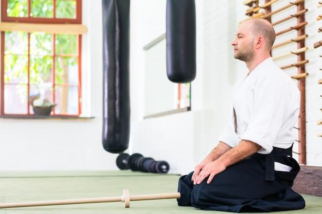 Homem, em, aikido, artes marciais, com, espada madeira