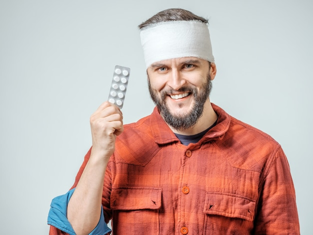 Homem em bandagem médica segurando comprimidos na mão