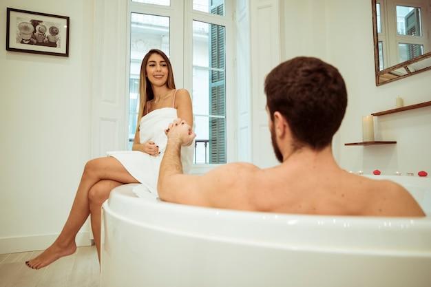 Homem, em, banheira spa, segurando mão, de, mulher sorridente