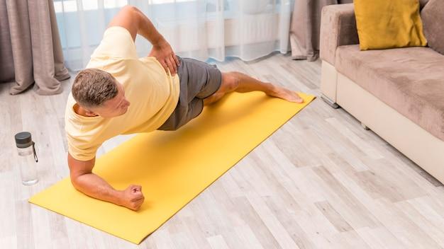 Homem em boa forma se exercitando em casa com garrafa de água e tapete