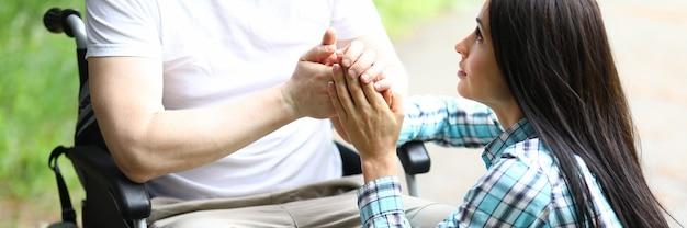 Homem em cadeira de rodas mantém as mãos juntas com a mulher amada.