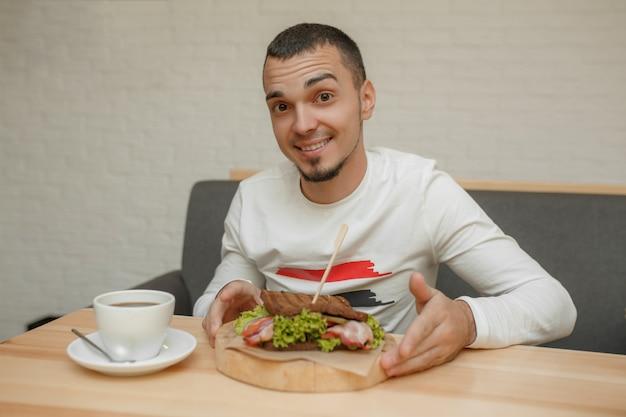 Homem, em, café, comer, sanduíche