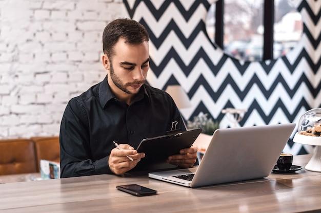 Homem, em, café, verificar, relatórios financeiros