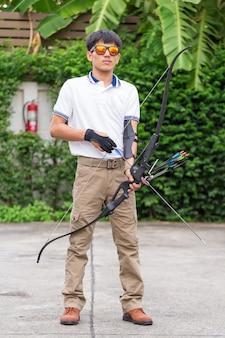 Homem em calças cargo com arco e flechas