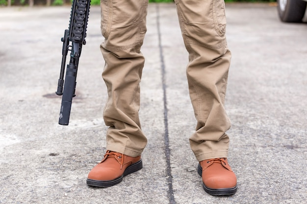 Homem, em, calças cargo, com, arma