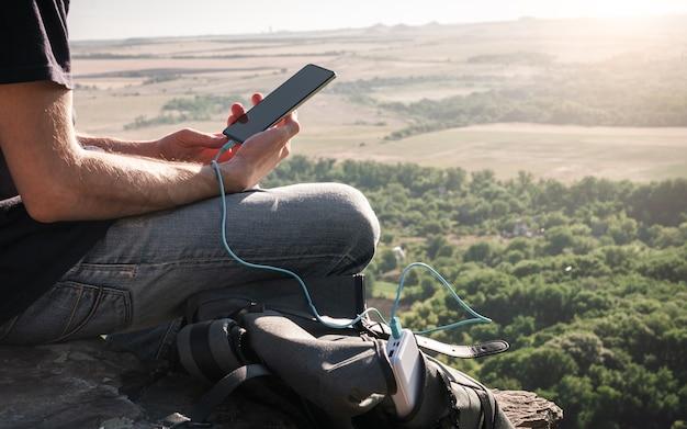 Homem em caminhada usa smartphone enquanto carrega do banco de energia na rocha ao amanhecer estilo de vida e comunicação saudáveis