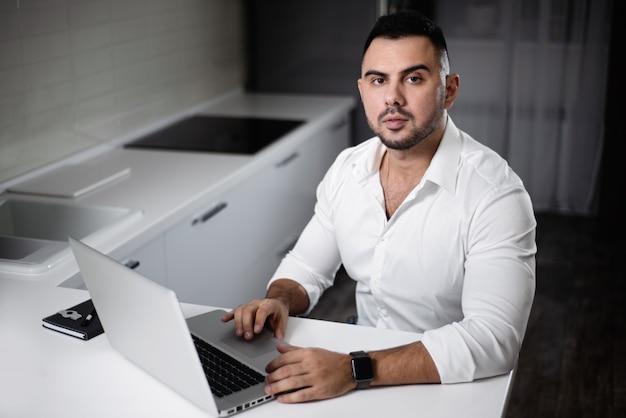 Homem, em, camisa branca, websurfing, com, laptop, em, lar, cozinha