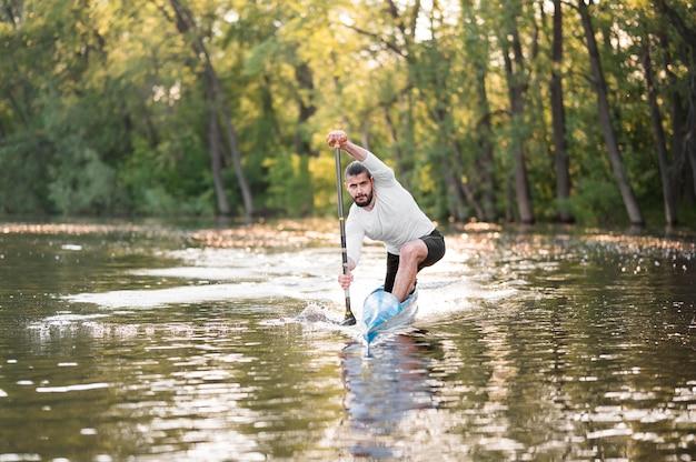 Homem em canoa, remar tiro no escuro
