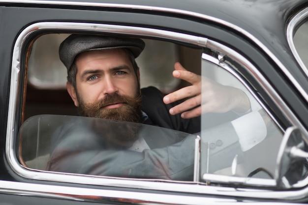 Homem em carro retrô, mostrando gesto comunicativo. modelo masculino vintage