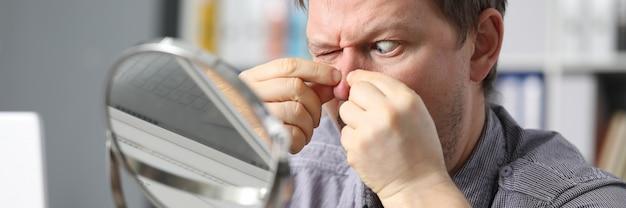 Homem em casa aperta os dedos acne no espelho frontal