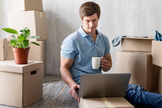 Homem em casa com laptop e caneca organizando caixas para se mudar
