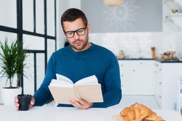Homem em casa com óculos lendo livro