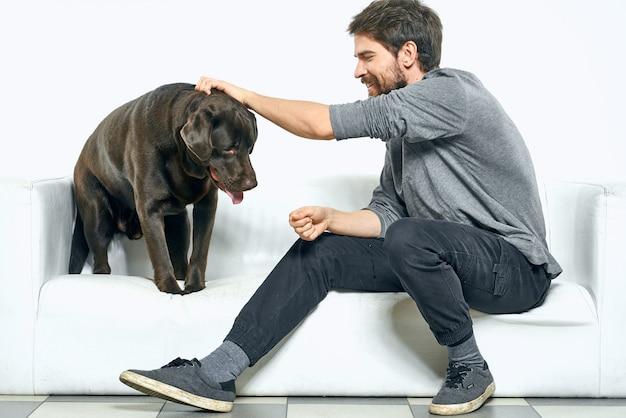 Homem em casa no sofá com seu cachorro descansando, treinamento de amizade. foto de alta qualidade