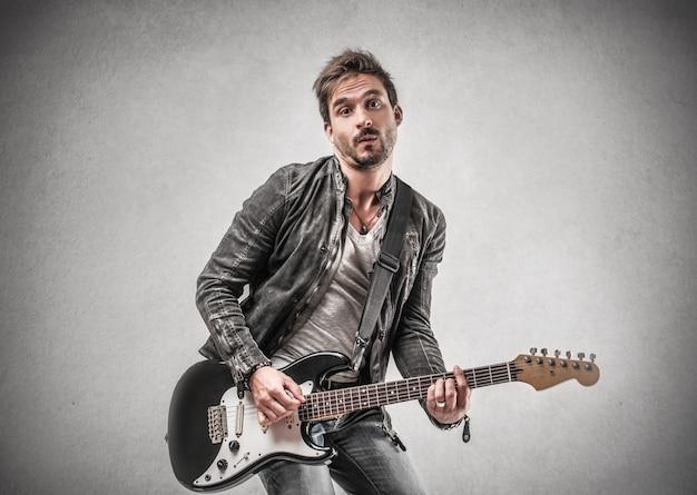 Homem, em, casaco couro, tocando, ligado, um, guitarra