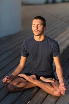 Homem em cena completa fazendo pose de sukhasana ao ar livre na doca