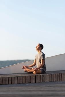 Homem em cena completa fazendo pose de sukhasana ao ar livre
