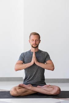 Homem em cena completa fazendo pose de sukhasana dentro do tapete