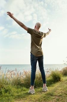 Homem em cena completa posando ao ar livre