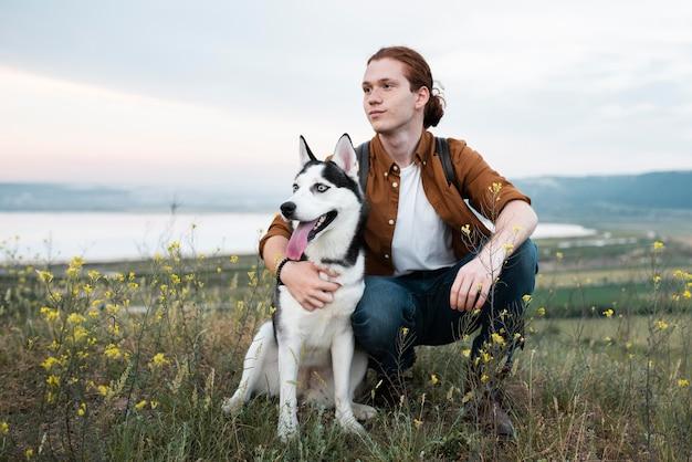 Homem em cena segurando um cachorro