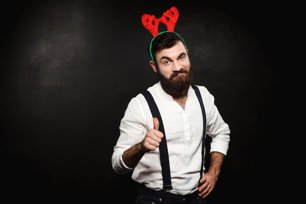 Homem em chifres de veado falso mostrando bem sobre preto.