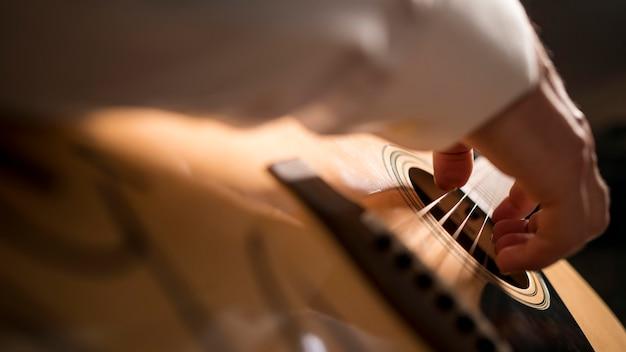 Homem em close de lado tocando guitarra