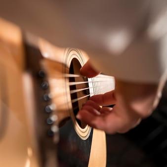 Homem em close-up extremo tocando guitarra
